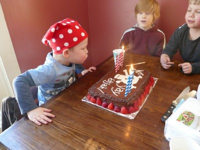 Lijah blowing out candles on his pirate cake
