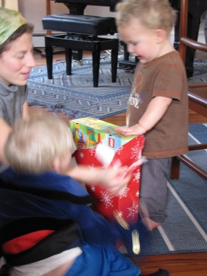 Lijah delightedly opening a present, Mama and Zion helping