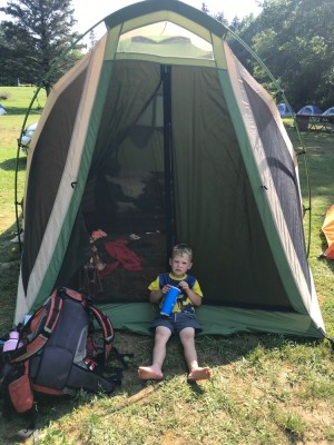 Lijah sitting in front of our tent looking tired