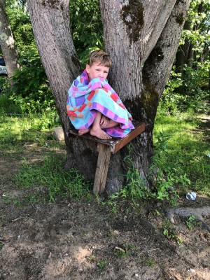 Lijah sitting on a bench in a tree wrapped up in a towel