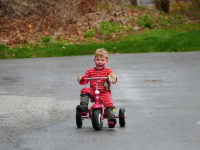 Lijah riding his red tricycle