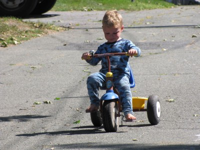 Lijah riding the older tricycle