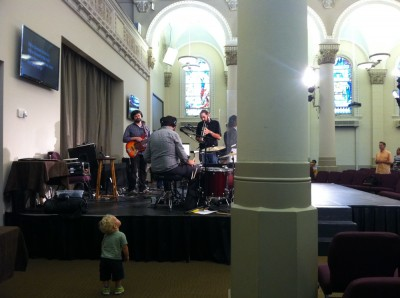 Lijah standing next to the stage at church during worship; the bass player is looking at him