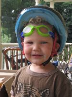 Lijah with his bike helmet on and swim goggles pushed up on his forehead
