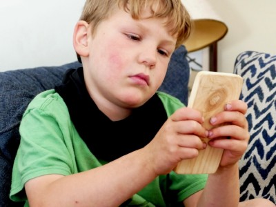 Elijah watching something on his wooden phone