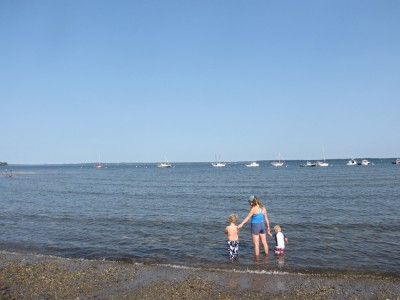 Leah and the boys wading in the ocean with boats moored in the background