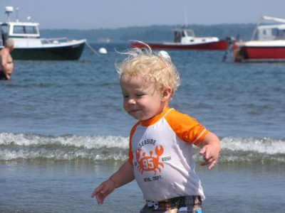 Zion running on the beach in Lincolnville, with lobsterboats in the background