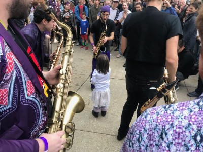 a young girl amidst the Party Band saxophonists