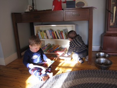 Lijah sitting on the living room floor reading a book, baby Joan Marc behind him