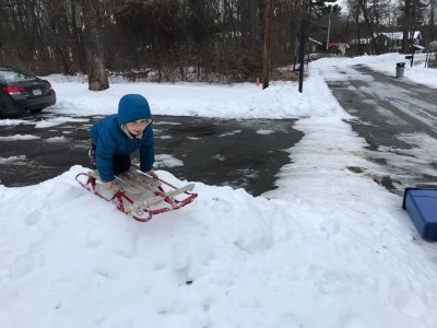 Zion on the runner sled atop a tiny mound of snow