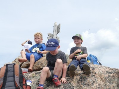 Lijah with his friends sitting on the cairn atop a mountain