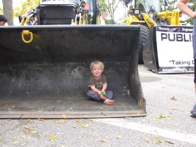 Zion sitting in the bucket of a front-end loader
