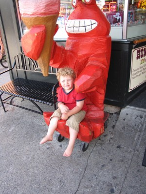 Harvey sitting in the lap of a big wooden lobster holding an ice cream cone (the lobster has the cone, not Harvey)