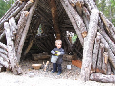 Lijah standing in a log wigwam-like structure