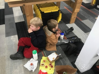 Zion and Lijah eating McDonalds on the floor of a game shop