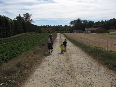 Mama, Zion, and Harvey walking down the path towards the apple trees