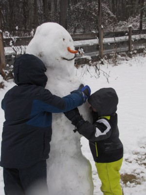 Harvey and Zion hugging their snowman