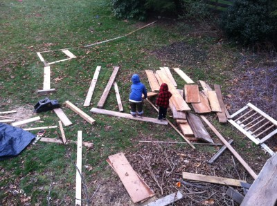 Harvey and Zion making roads and ramps for little cars out of the piles of lumber on the lawn