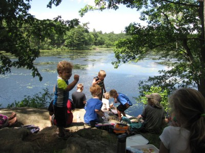 the kids eating lunch on the little cliff above the pond