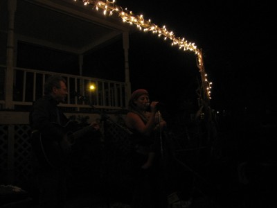 Leah singing with her dad, lit by the Christmas lights