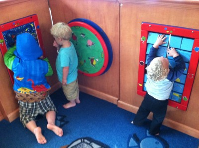 three boys at the activity wall of the mall play space