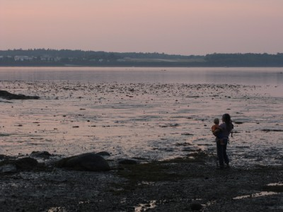 Leah, holding Lijah, watching the sunset at low tide