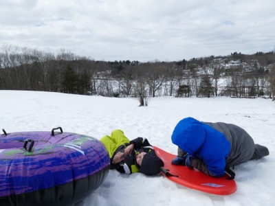 Zion and Harvey lying down at the top of the sledding hill