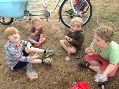 Nathan and the three boys eating donuts on the grass at the farmers market