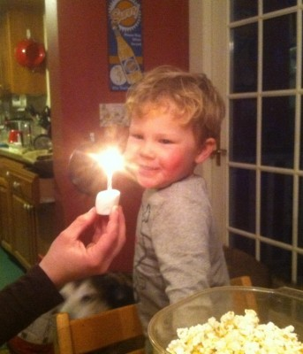 Lijah smiling at a candle burning in a marshmallow held before him