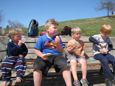 the boys eating matzah sandwiches at a playground