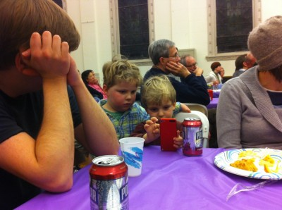 Harvey and Eliot sharing an iPhone during a church meeting