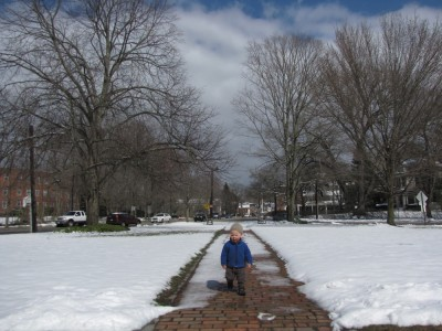 Lijah on the path to the library in Concord--sun shining, snow melting fast