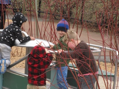 Harvey and Zion and a couple other boys cooperating on the playground merry-go-round