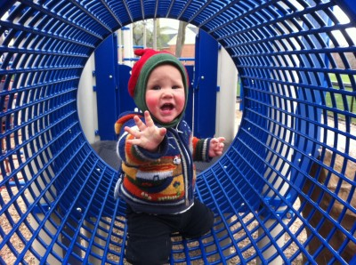 Lijah in the cage tube at the playground, reaching for the camera