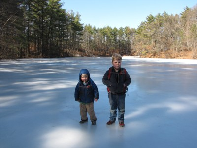 Harvey and Zion standing on the ice at the middle of the pond