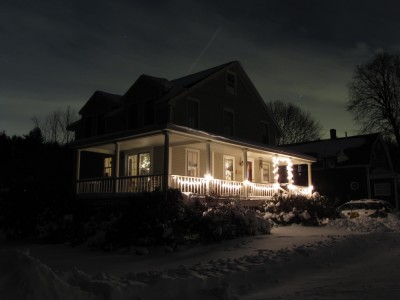 our house, with Christmas lights, in the snow