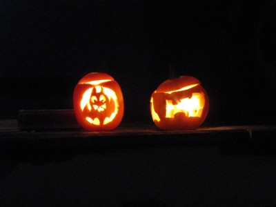 glowing jack-o-lanterns: a bat and an H carved and illuminated in little pumpkins