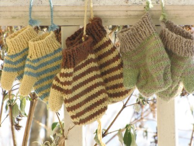 three pairs of mittens hanging on the porch rail