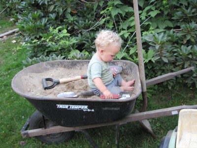 Lijah playing in a dirt-filled wheelbarrow, with shovels