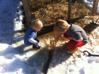 Zion and Harvey chipping ice around a muddy puddle