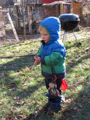 Lijah outside with a monkey toy hanging from his coat pocket