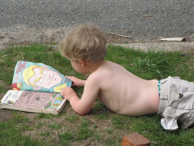 shirtless Zion lying in the front yard reading a comic