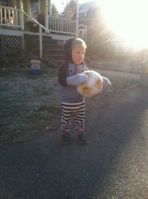 Lijah in pjs and sweatshirt holding a soccer ball in front of the house