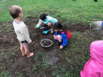 Lijah playing in the mud with other kids at Park Day