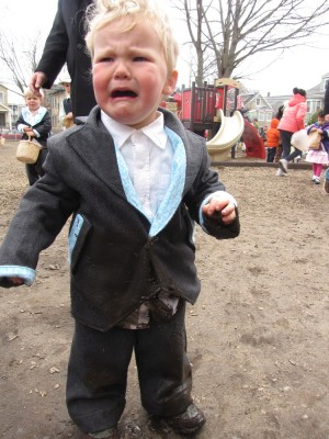 Lijah crying, with mud all over the front of his suit