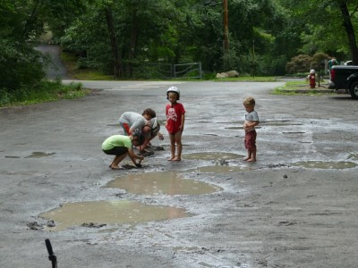the boys with friends playing in a muddy parking lot