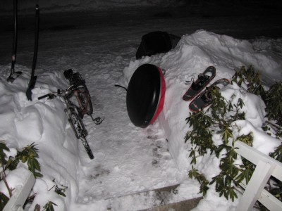 bike, sled, and snowshoes in the evening snow