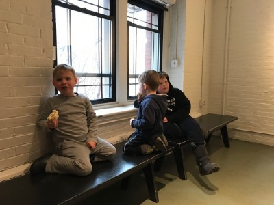 the boys eating a snack in the bare lobby of the HMNH