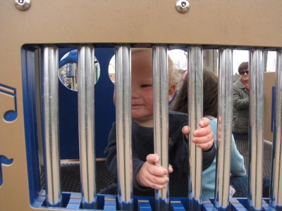 Lijah behind the tubular bell bars at the playground