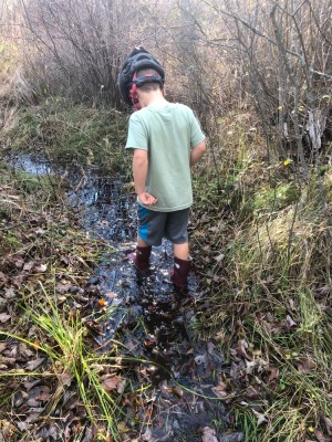 Elijah wading in a stream in his boots